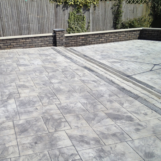 Imprinted slate grey concrete patio with built in Aco drianage channels